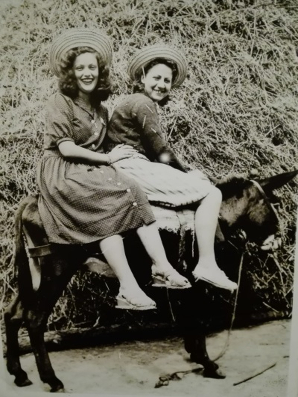 Gloria Fuertes y una amiga sobre un burro hacia 1940